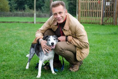 Chris Packham playing with one of the many dogs at Blue Cross rehoming centre, Southampton