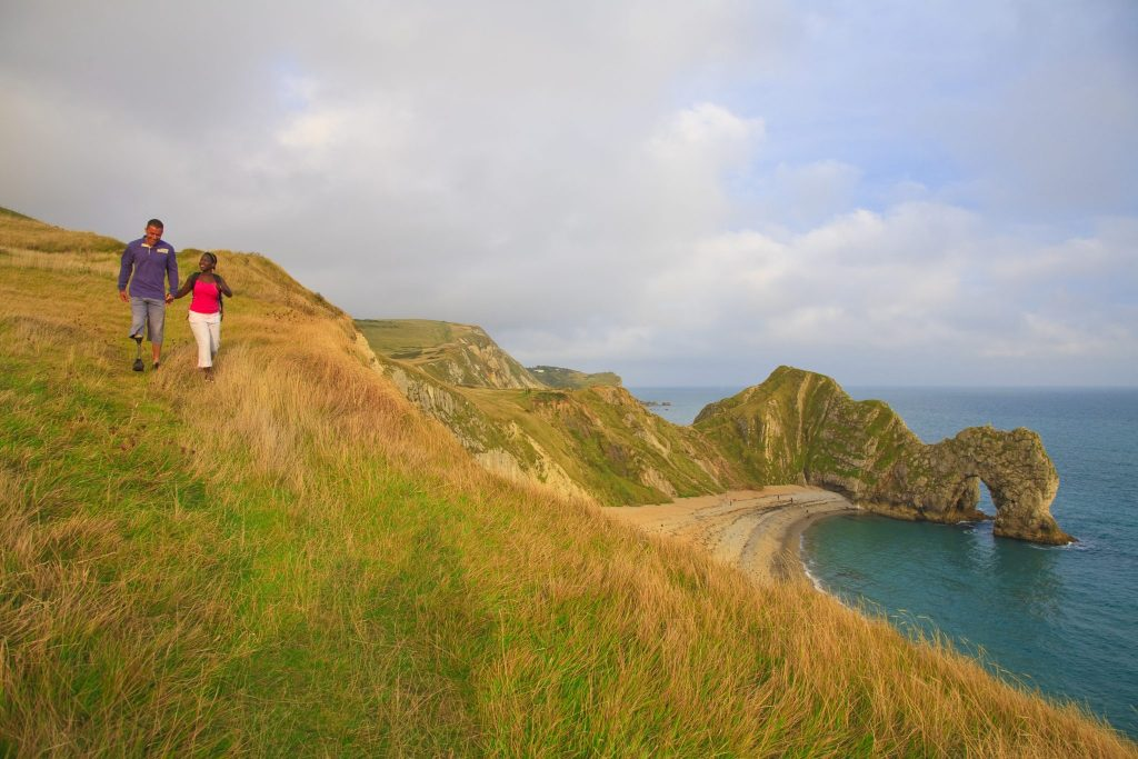 A couple walking on the clifftop above Durdle Door on the Jurrassic coast of Dorset. The man is a right below knee amputee and the woman is profoundly deaf., Durdle Door, Dorset, England. Additional Credit: Tourism For All