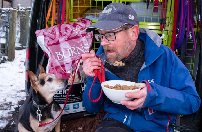 Nick Pearson with a bowl of kibble and his Jack Russell cross Basil
